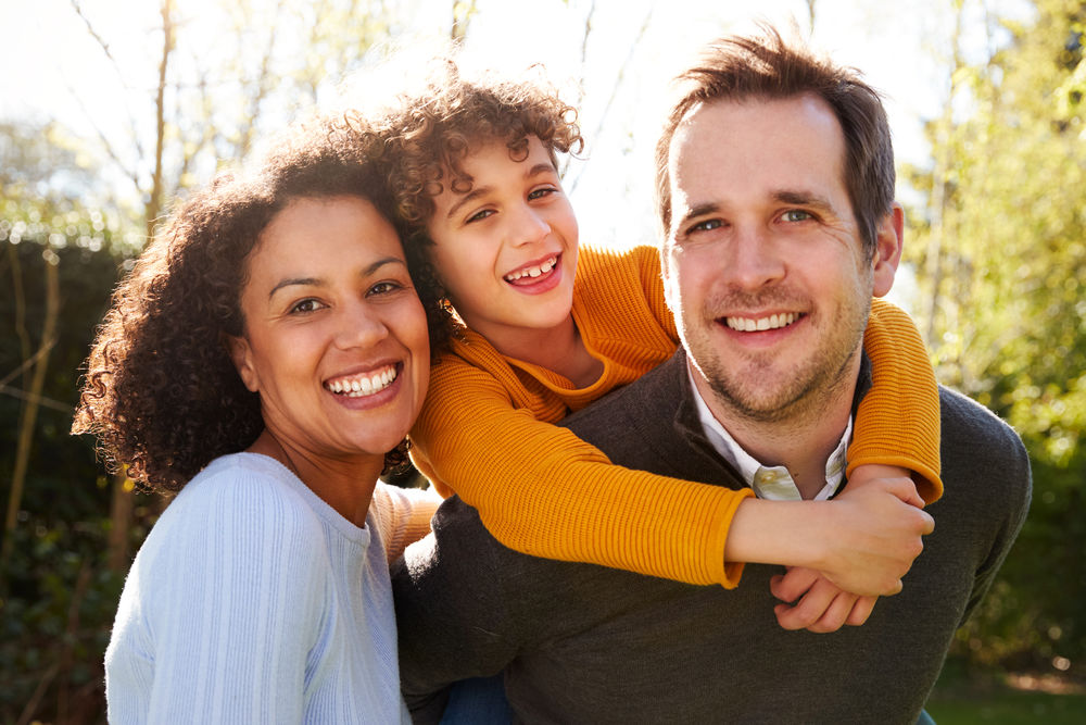 Outdoor Portrait Of Smiling Family In Garden At Home Against Flaring Sun